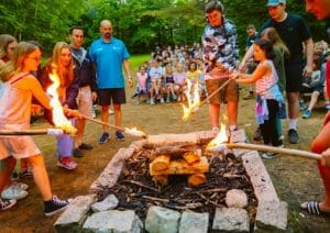 Campers, staff, and director roasting marshmallows by the campfire
