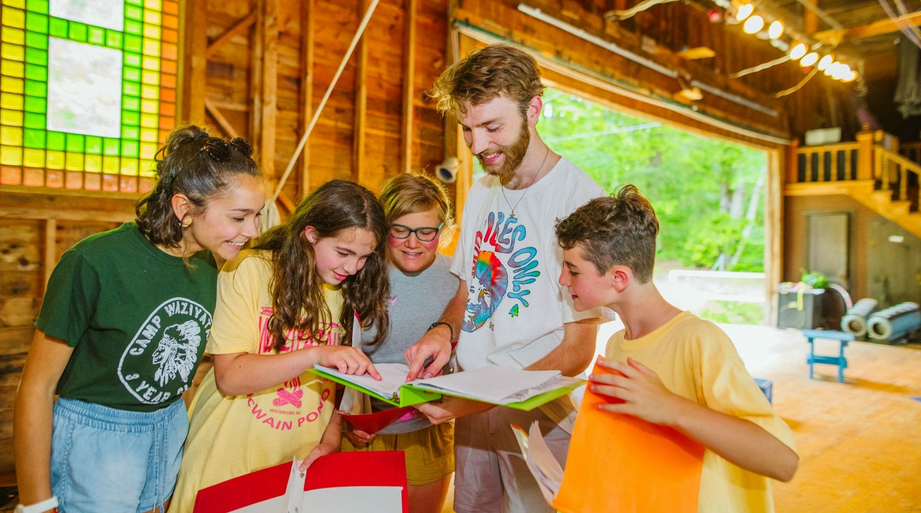 Staff and campers reading a script for acting