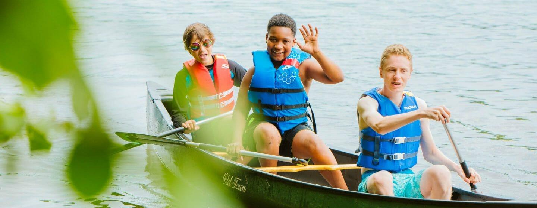 Three boys canoeing on the lake at Waziyatah