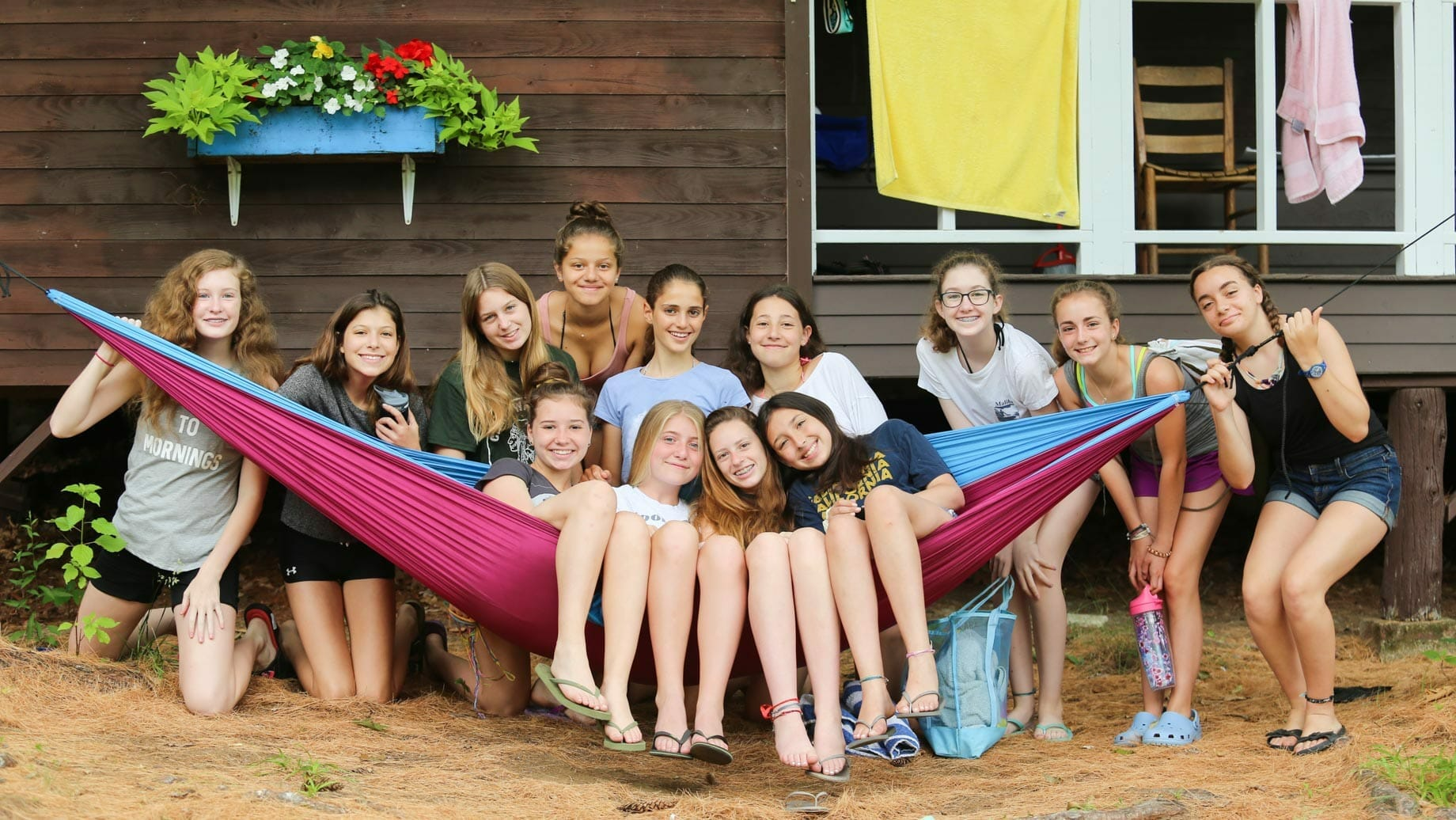 Girls posing on hammock by cabin