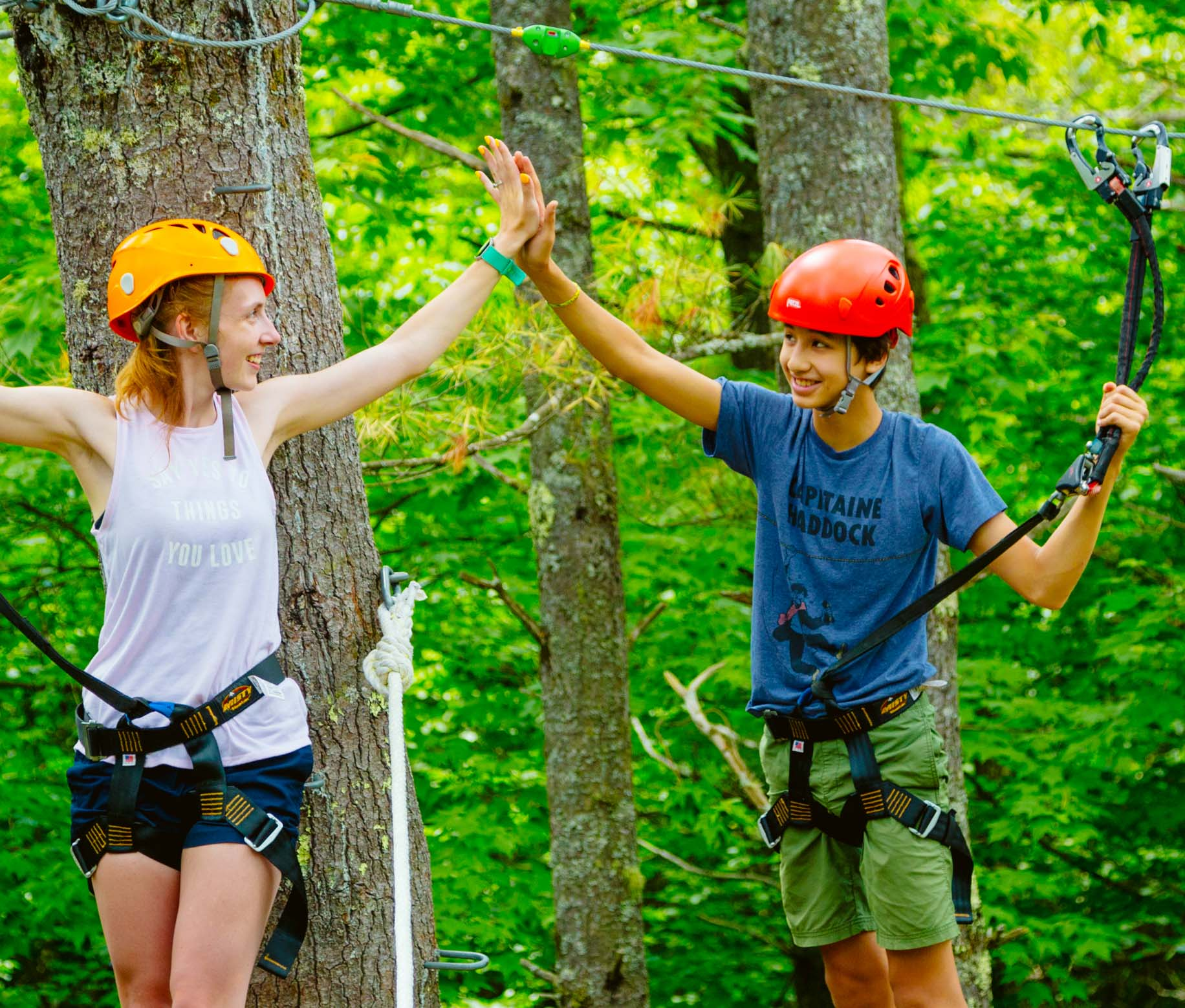 Two campers high fiving on the ropes course