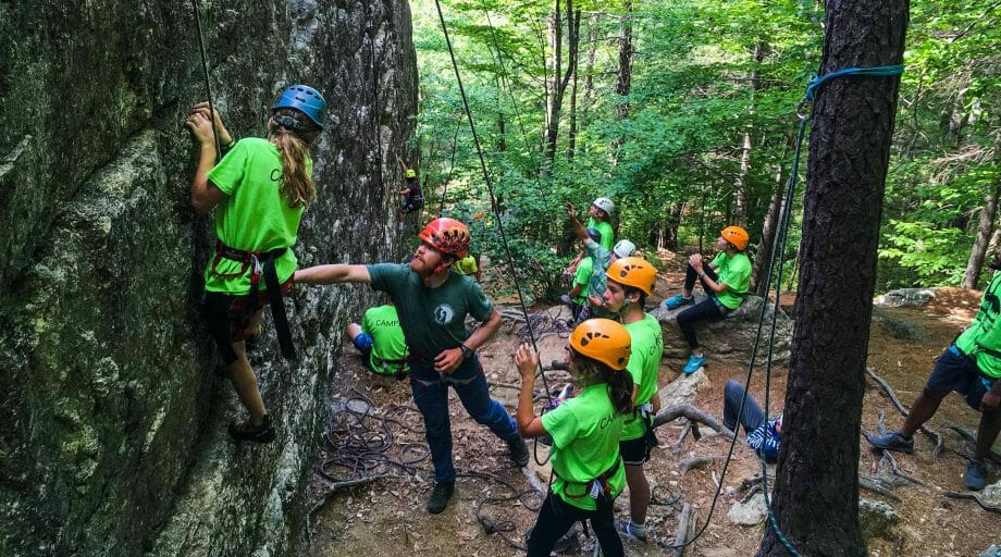 Campers climbing a rock wall on an off-camp trip