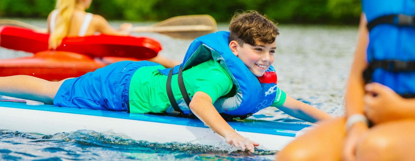 Boy laying on stand up paddleboard