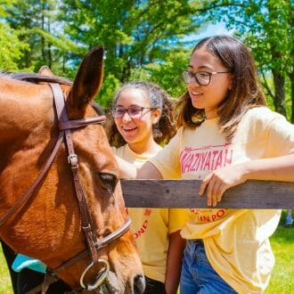 Girls petting a horse