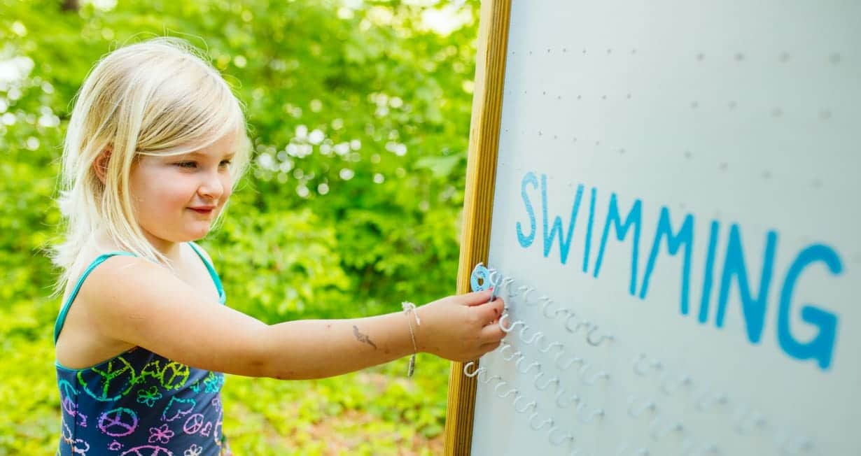 Girls marking down which swimming activity they are doing