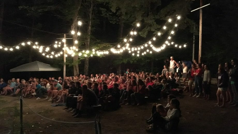 Audience watching an outdoor theater performance at night