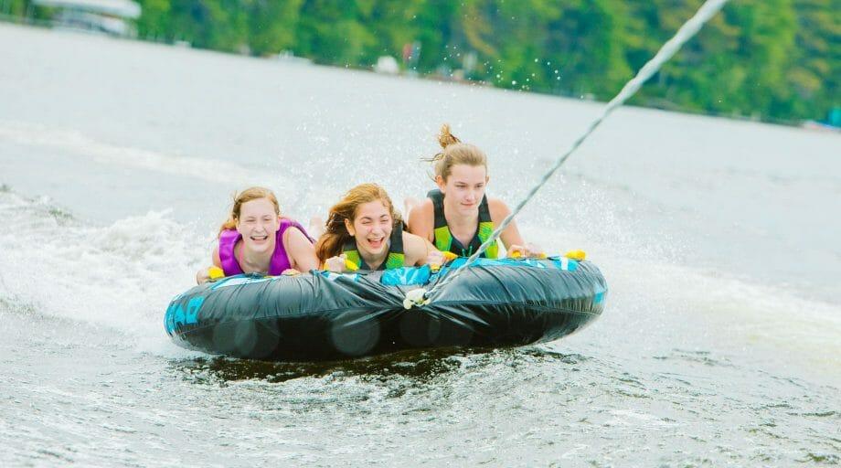 3 girls water tubing on the lake