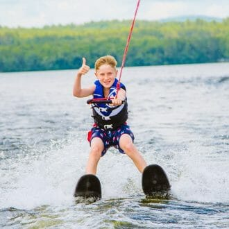 Boy waterskiing and giving thumbs up