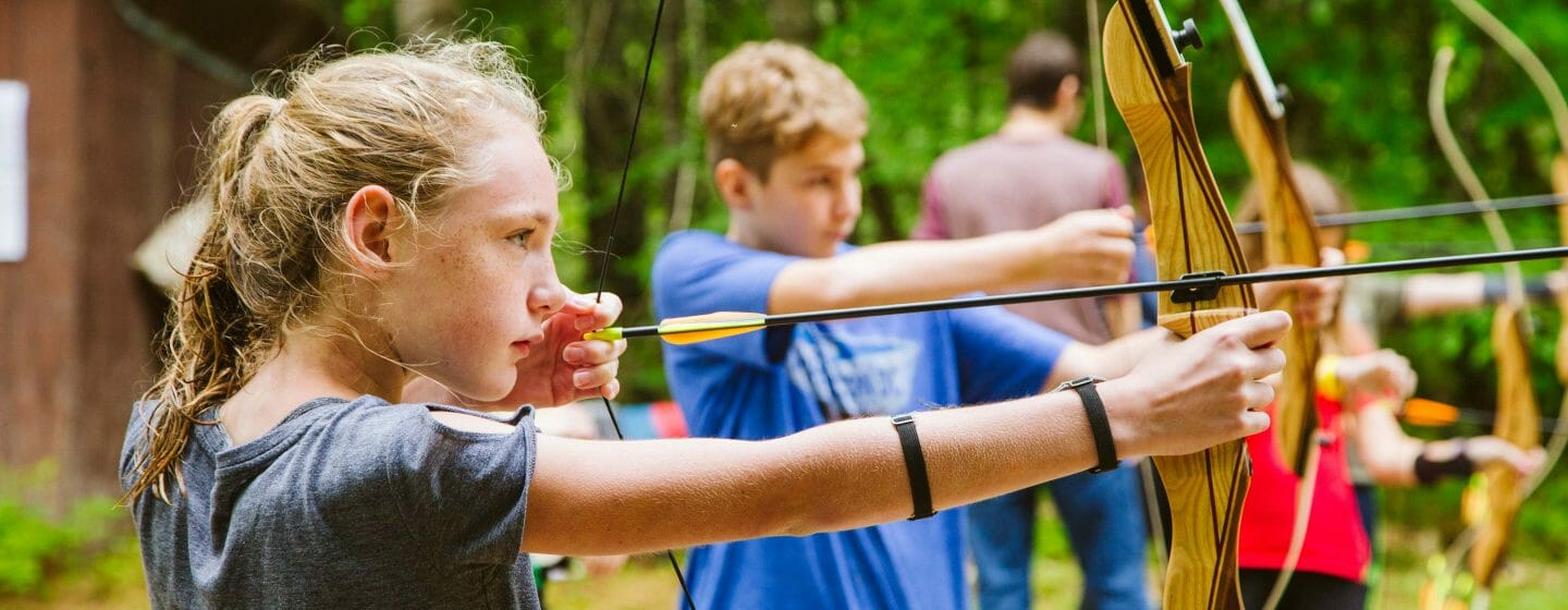 Girl with other campers practicing archery shots