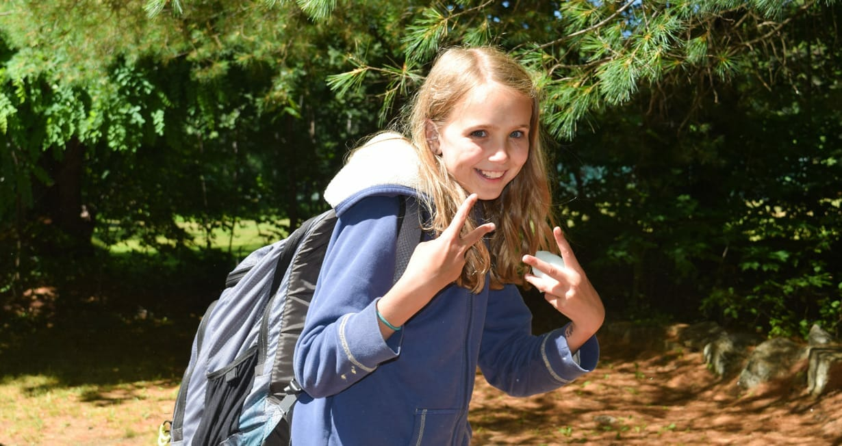 Camper giving the peace sign and wearing a backpack on arrival day