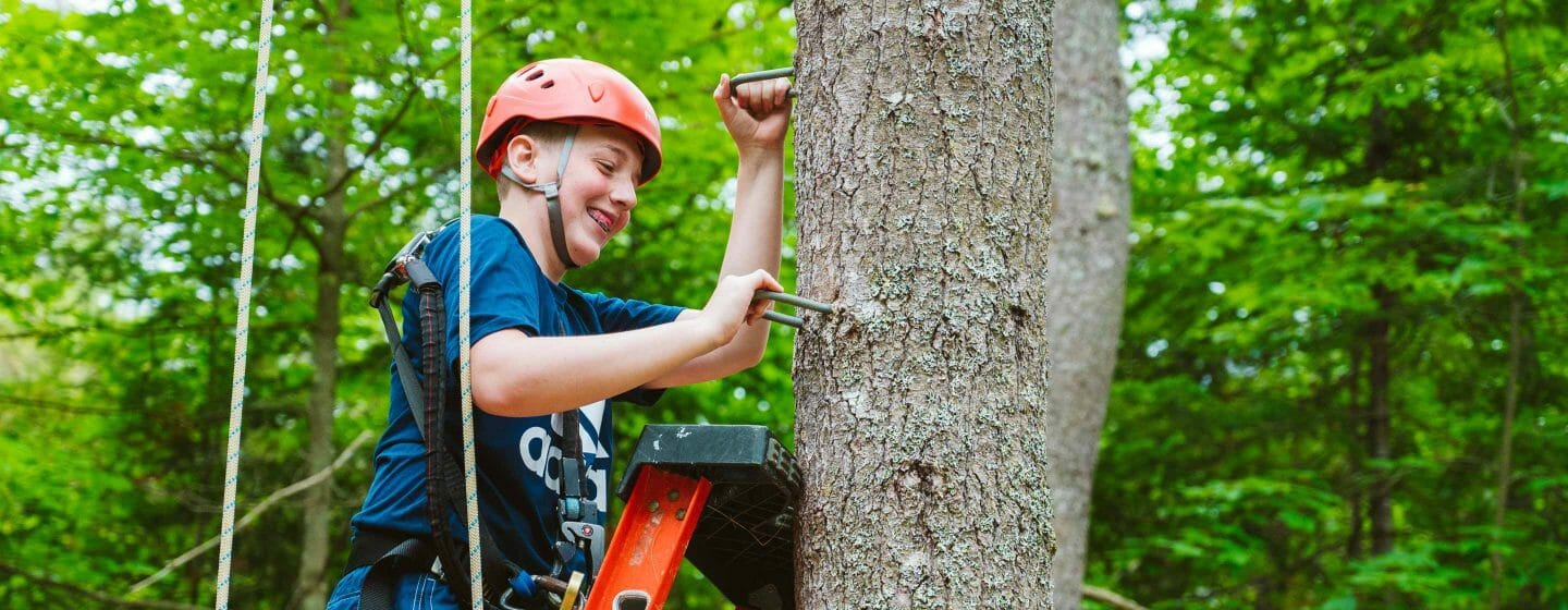 Male camper climbing ladder and tree to high ropes course