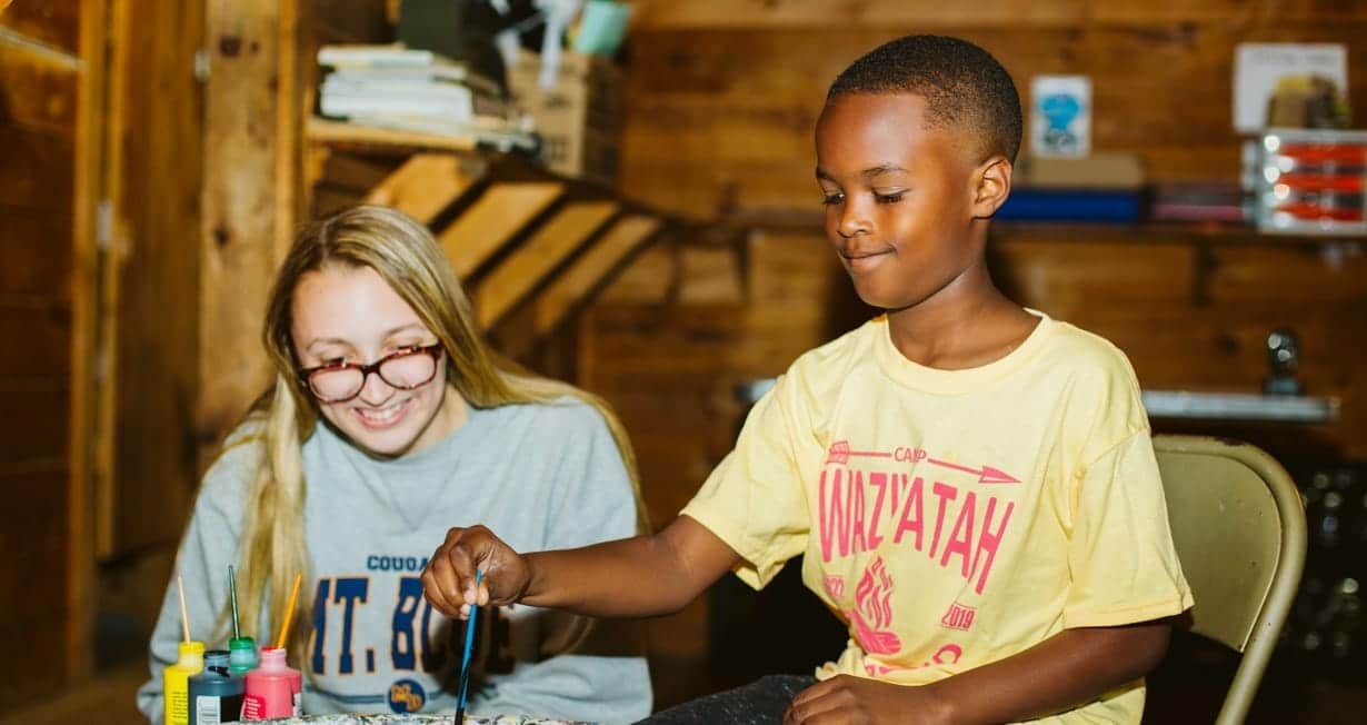Arts and crafts instructor teaching a camper how to use the pottery wheel