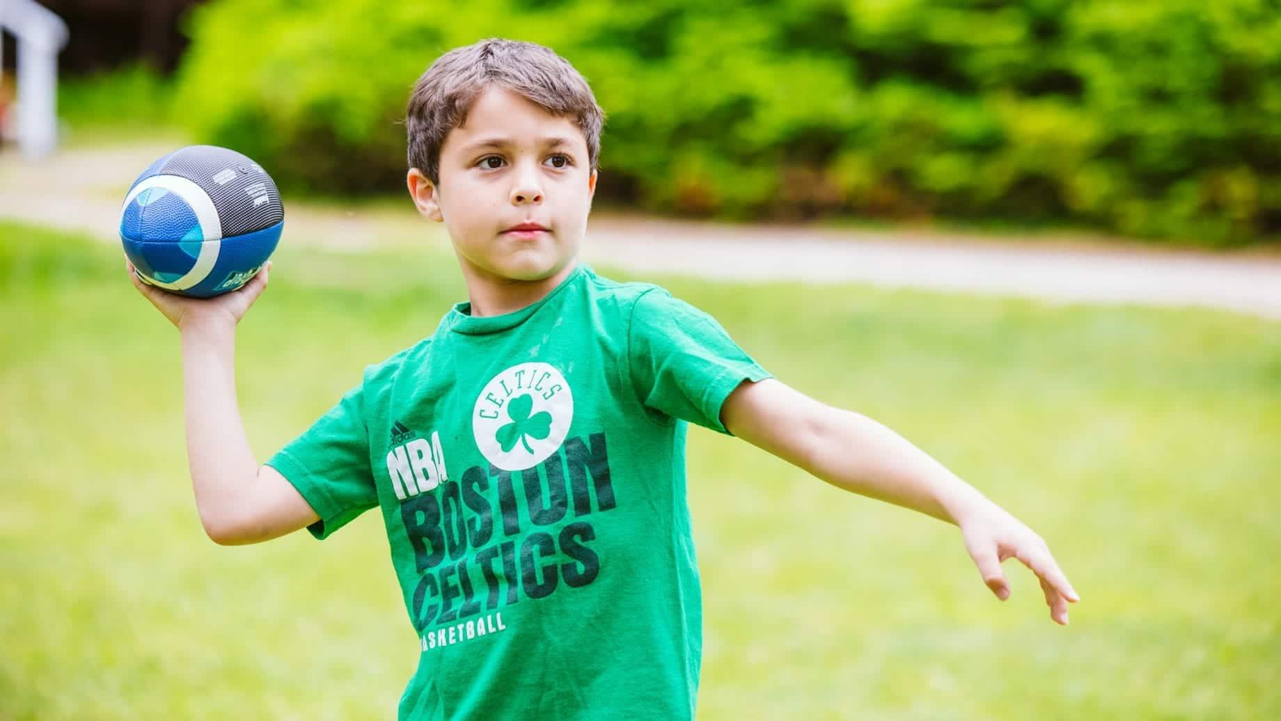 Young boy playing football at Camp Waziyatah
