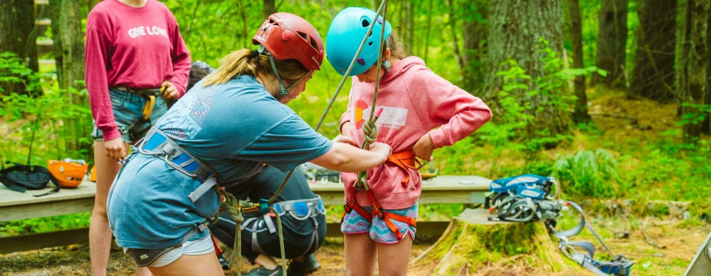 Staff helping camper put her climbing harness on