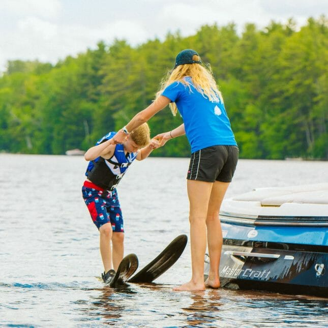 Staff helping a camper with water skiing