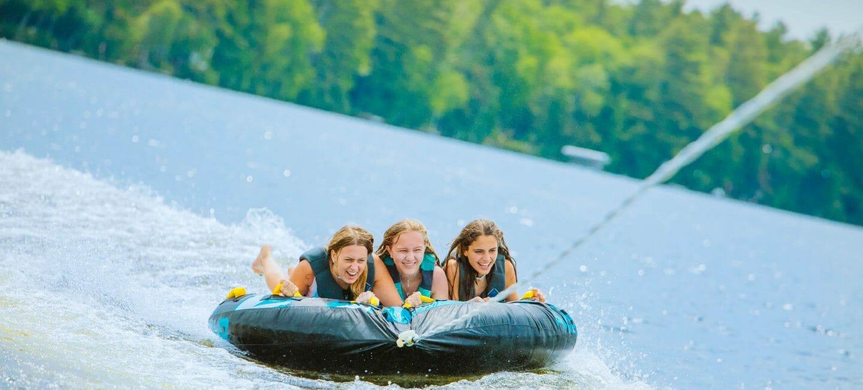 Three girls water tubing on lake