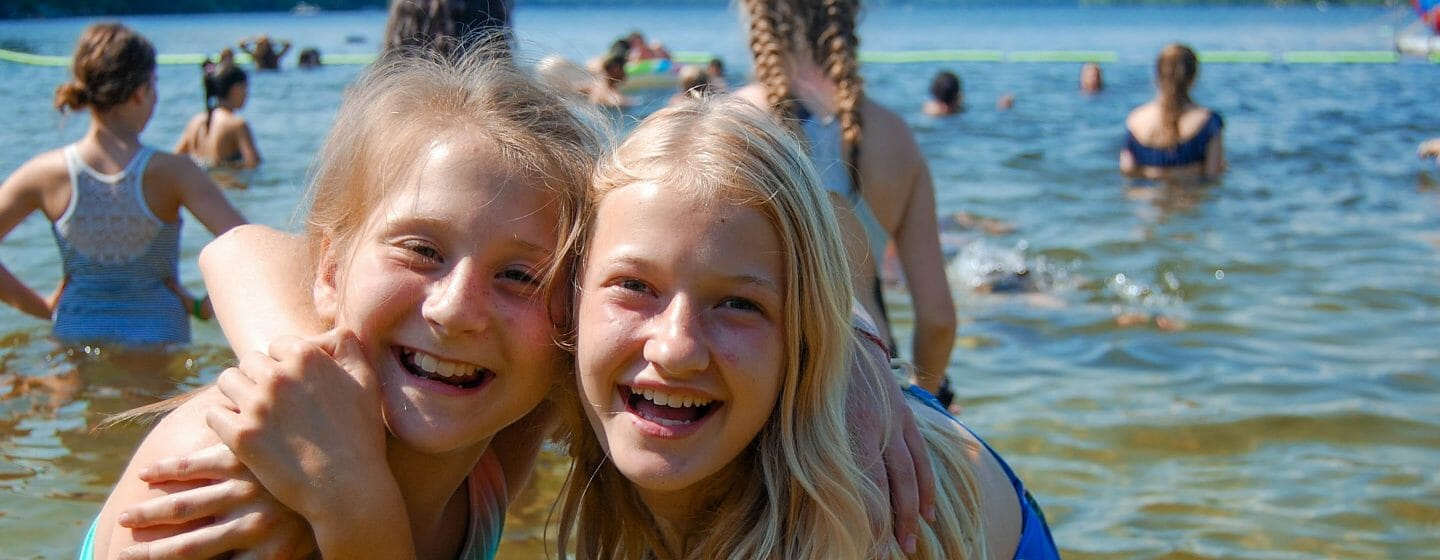 Two girls hugging each other at the waterfront with campers boating and swimming behind them