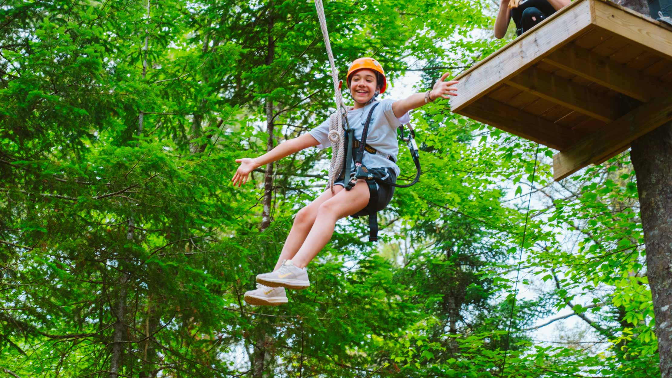 Girl zip lining with her arms stretched out