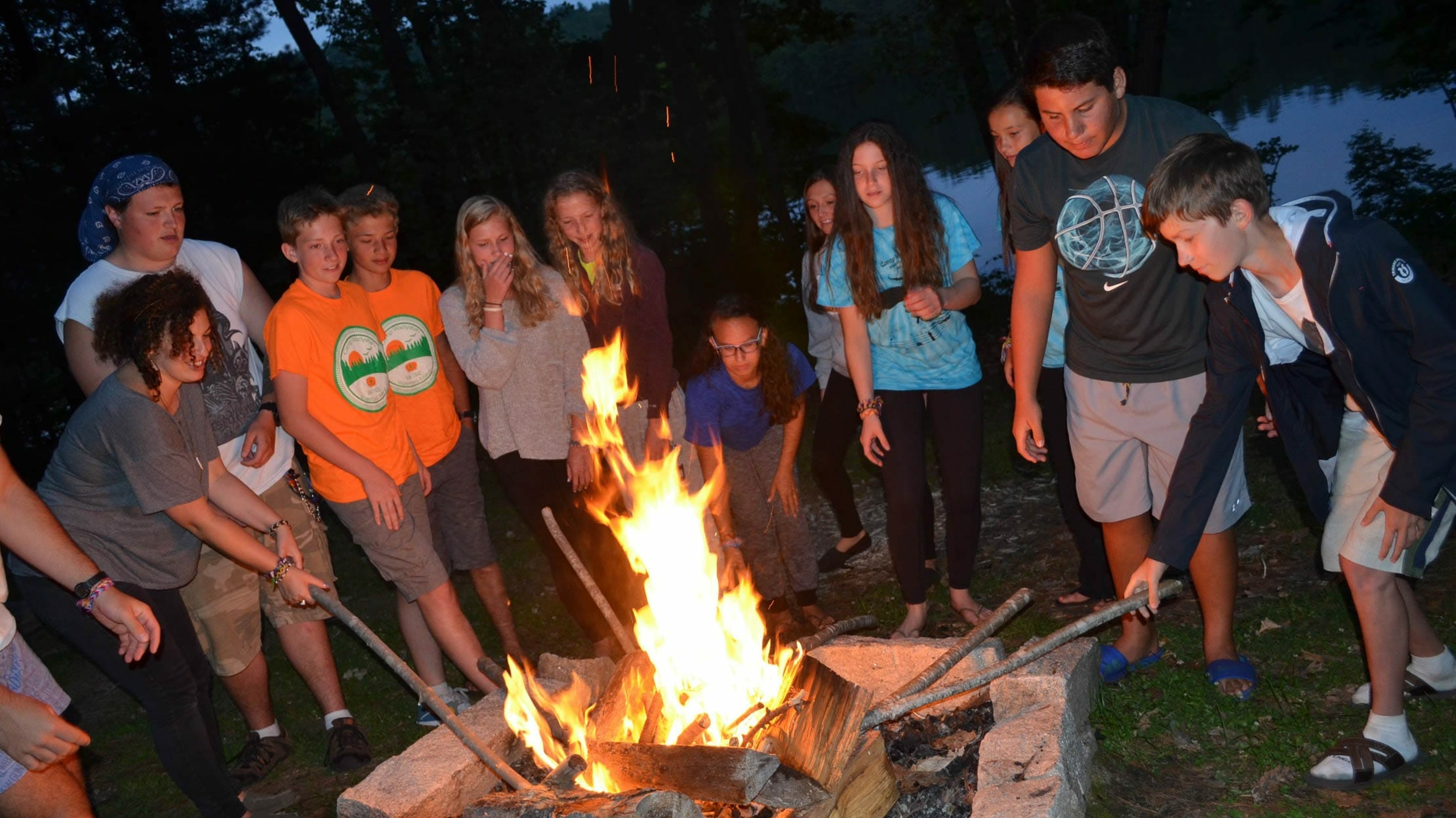 Campers at campfire roasting marshmallows