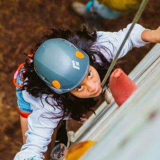 Girl climbing the rock tower