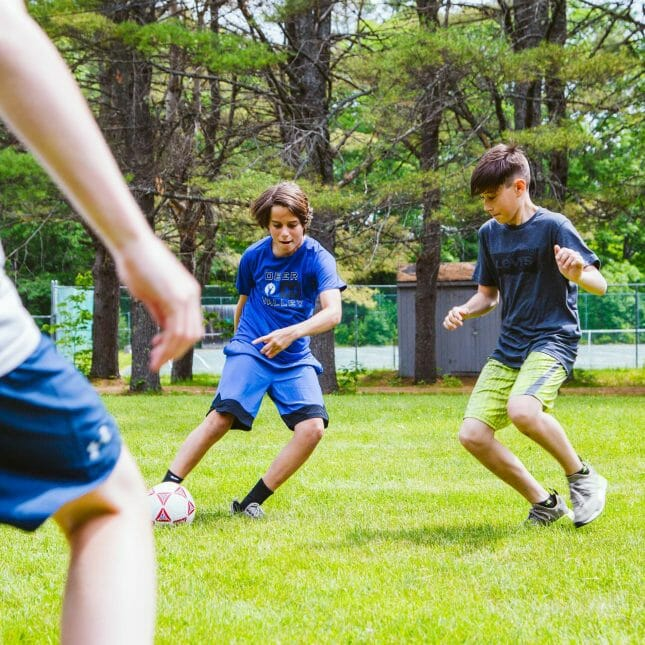 Two boys playing soccer on the field
