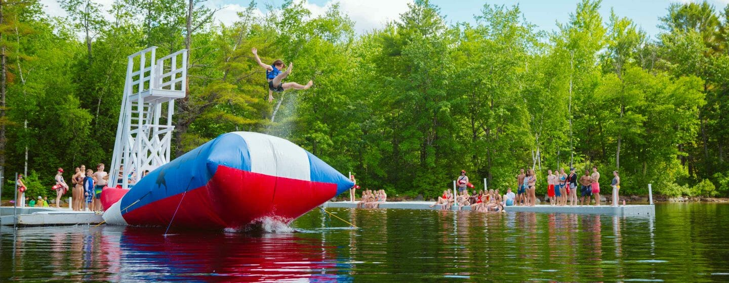 Boy being launched from The Blob at camp