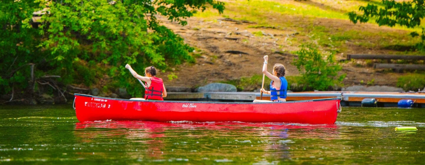 Two girls canoeing on the lake